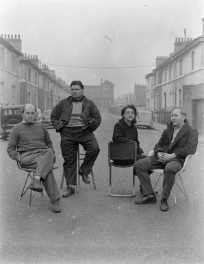 Nigel Henderson, Photograph showing Nigel Henderson, Eduardo Paolozzi, Alice and Peter Smithson, seated in an unidentified street (c.1949-c.1956) © Nigel Henderson Estate and Photographic Rights © Tate (2015). Available under a CC-BY-NC-ND 3.0 (Unported) licence Photo credit: http://www.tate.org.uk/art/archive/tga-201011-3-1-73-4/photograph-showing-nigel-henderson-eduardo-paolozzi-alice-and-peter-smithson-seated-in-an